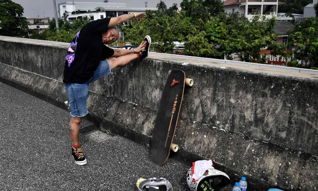 Jeab faz alongamento antes de sess?o de treinamento em avenida vazia de Bangkok Foto: LILLIAN SUWANRUMPHA / AFP