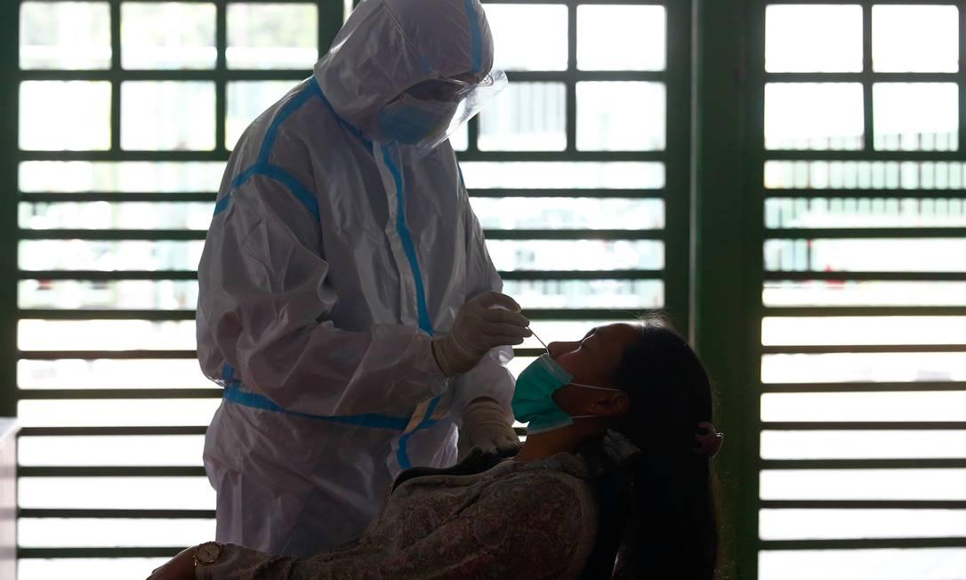 Um trabalhador de saúde usando equipamento de proteção coleta uma amostra para testar uma pessoa para a Covid-19 Foto: Ajeng Dinar Ulfiana / Reuters