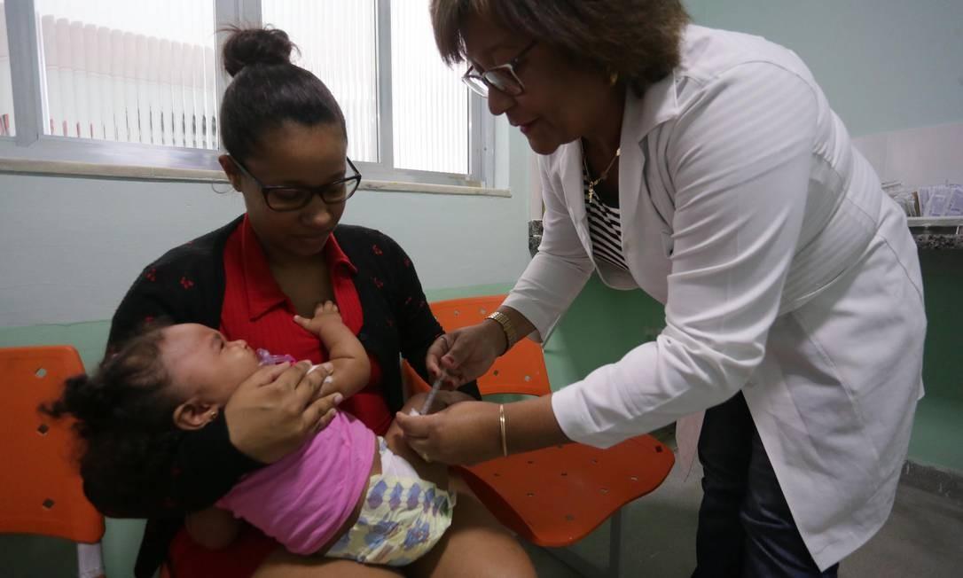 Enfermeira aplica vacina tríplice viral em criança em posto de saúde em Berlford Roxo (RJ), na Baixada Fluminense, em foto de julho de 2018 Foto: Cléber Júnior / Agência O Globo