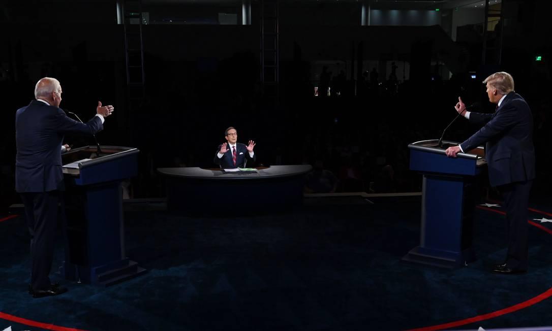 Moderador do debate da noite de terça-feira, Chris Wallace (C), faz advertência ao presidente Donald Trump (D) depois de interrupção durante resposta do democrata Joe Biden (E) Foto: OLIVIER DOULIERY / AFP