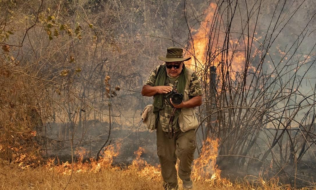 O fotógrafo Araquém Alcântara em ação numa área atingida pelas queimadas, na região da Rodovia Transpantaneira, no Mato Grosso Foto: Acervo pessoal
