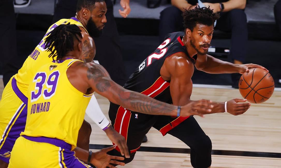 Jimmy Butler, principal destaque do Miami Heat, tenta passar por LeBron James e Dwight Howard, do Lakers, no primeiro jogo da final da NBA Foto: Kevin C. Cox / AFP