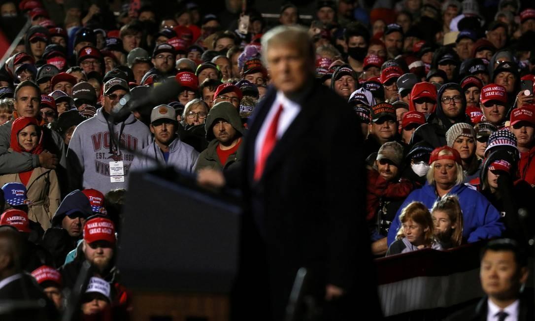 Aglomerados e sem máscara, apoiadores de Trump observam enquanto o presidente e candidato à reeleição discursa durante um comício de campanha no Aeroporto Internacional de Duluth, no estado de Minnesota Foto: LEAH MILLIS / REUTERS
