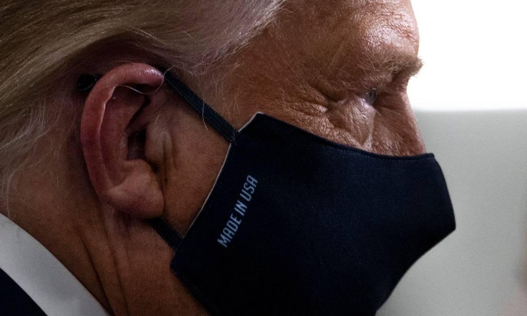 """Trump, em foto de 6 de agosto, usa uma máscara que diz """"feito nos EUA"""" enquanto visita uma fábrica da Whirlpool Corporation, em Clyde, Ohio Foto: JIM WATSON / AFP"""