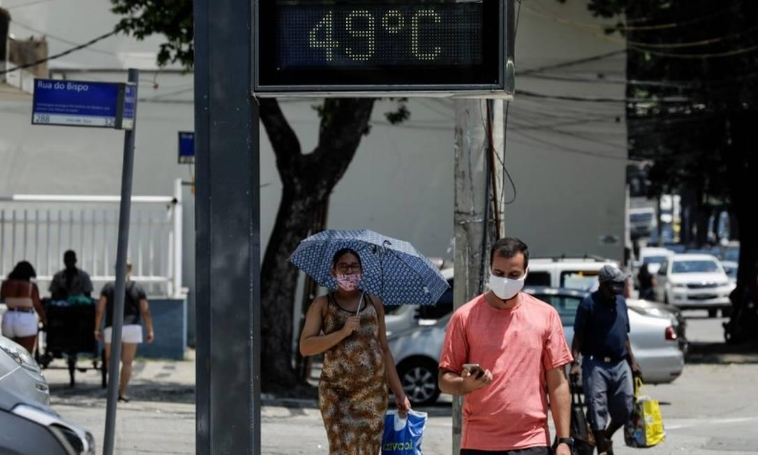 Termômetro de rua marca 49 graus no Estácio. Pedestre usa guarda-chuva para se proteger do sol Foto: Gabriel de Paiva / Agência O Globo