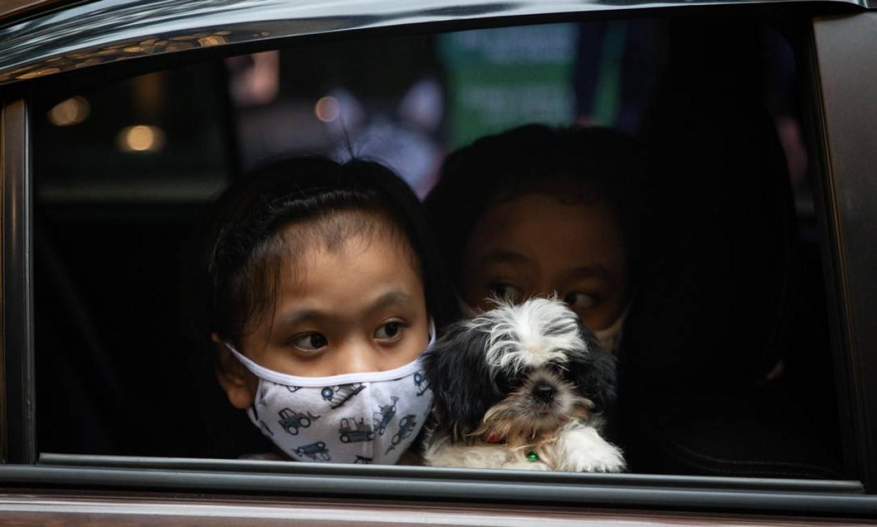Crianças com máscaras de proteção e de dentro do veículo aguardam momento de levar cachorrinho para ser abençoado por padre. Foto: ELOISA LOPEZ / REUTERS