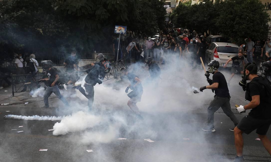 Manifestantes são vistos correndo em meio ao gás lacrimogêneo em Atenas Foto: COSTAS BALTAS / REUTERS