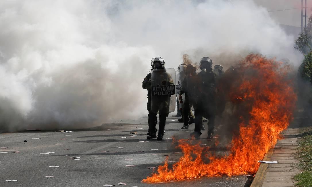 Policiais da tropa de choque são vistos entre chamas e fumaça de gás usada para dispersar manifestantes Foto: COSTAS BALTAS / REUTERS