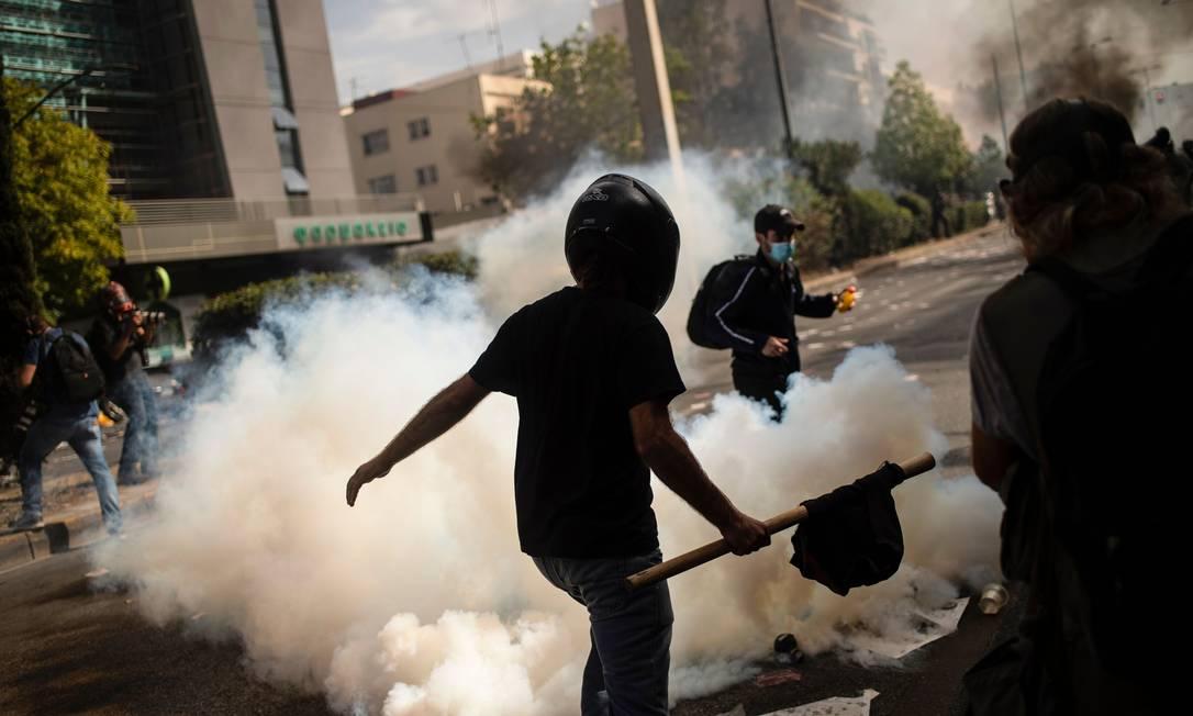 Manifestantes fogem de bomba de gás atirada pela polícia Foto: ANGELOS TZORTZINIS / AFP