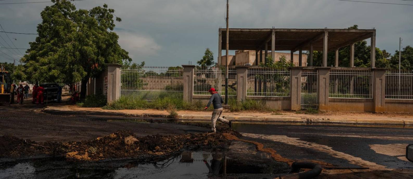 Homem anda próximo a poças de óleo na cidade Cabimas, na Venezuela Foto: ADRIANA LOUREIRO FERNANDEZ / NYT