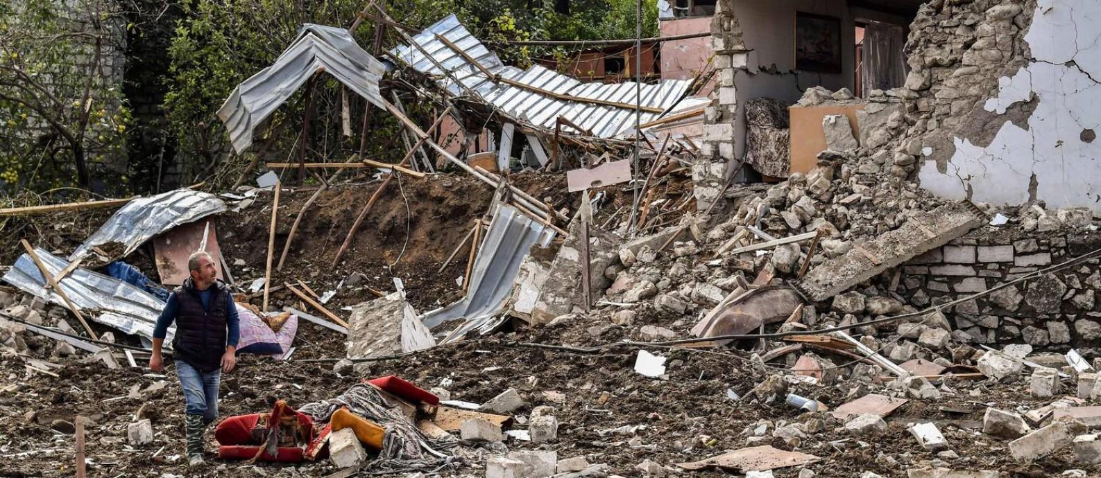 Homem caminha pelos destroços de um bombardeio em Stepanakert, principal cidade separatista da região de Nagorno-Karabakh Foto: ARIS MESSINIS / AFP/08-10-2020