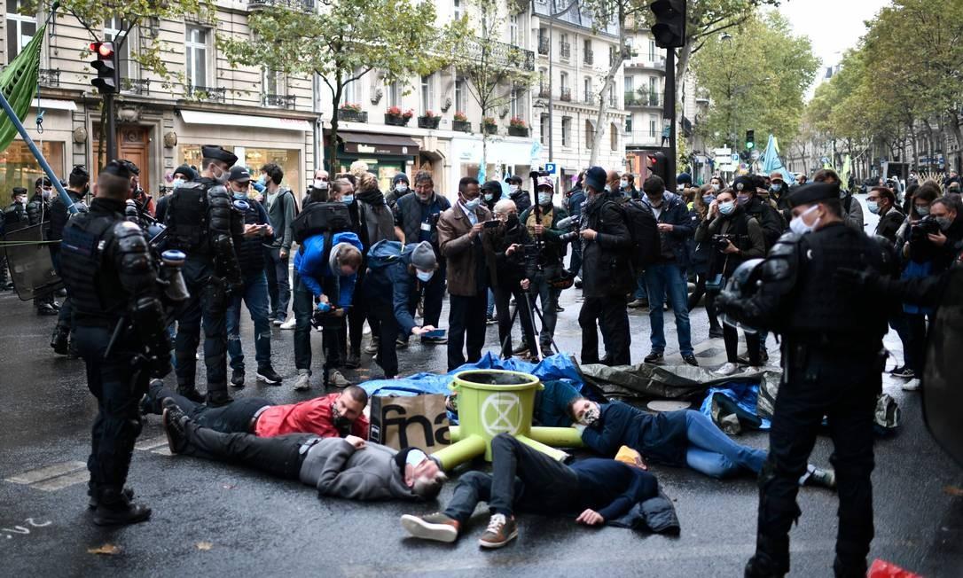Ativistas são cercados por policiais franceses, durante ato em frente ao Ministério da Ecologia, em Paris Foto: STEPHANE DE SAKUTIN / AFP