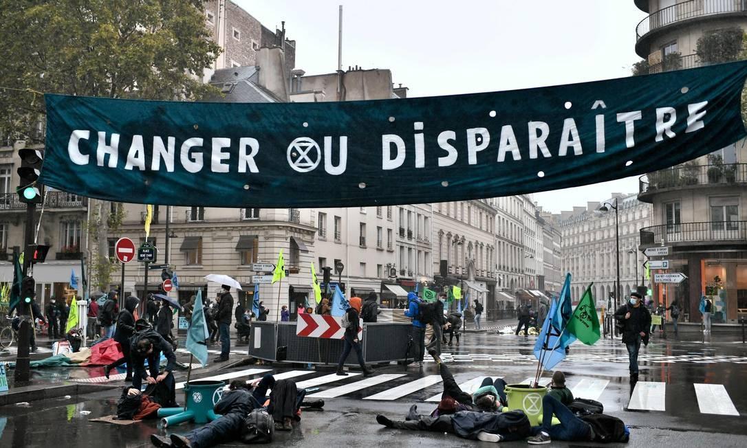 'Mude ou desapareça', diz a faixa em uma rua de Paris Foto: STEPHANE DE SAKUTIN / AFP