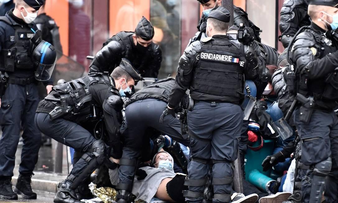 Ativista do grupo Rebelião da Extinção é detido por policiais em uma rua de Paris Foto: STEPHANE DE SAKUTIN / AFP
