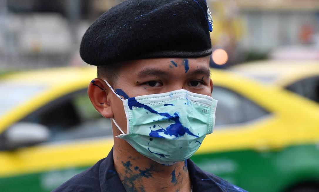 Policial atingido por tinta azul atirada por manifestantes faz guarda à espera da passagem da comitiva real, em Bangcoc Foto: MLADEN ANTONOV / AFP