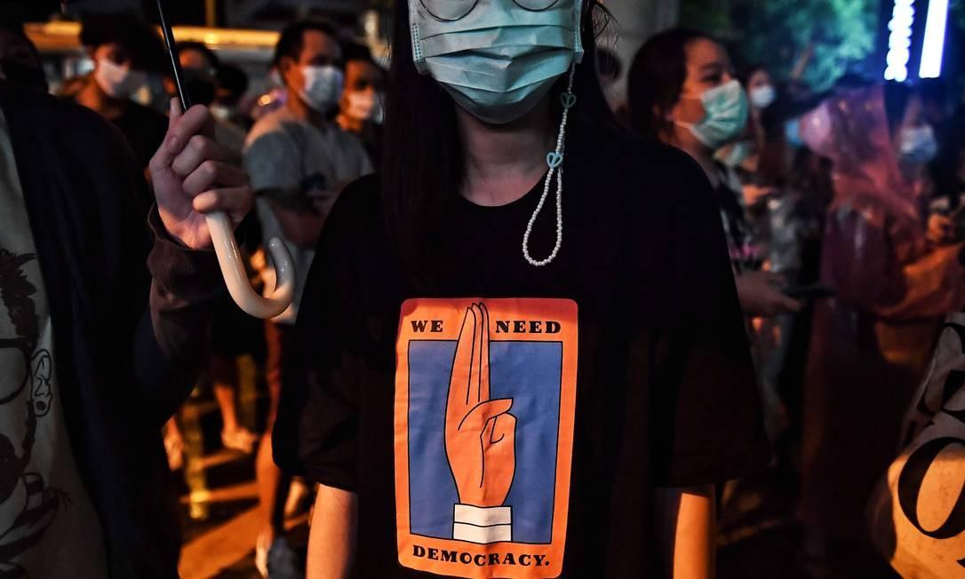 Uma mulher usa uma camiseta com desenho da saudação de três dedos para protestar, em frente à sede da polícia de Bangcoc, contra a prisão de manifestantes pró-democracia durante protestos desta terça-feira contra monarquia Foto: LILLIAN SUWANRUMPHA / AFP