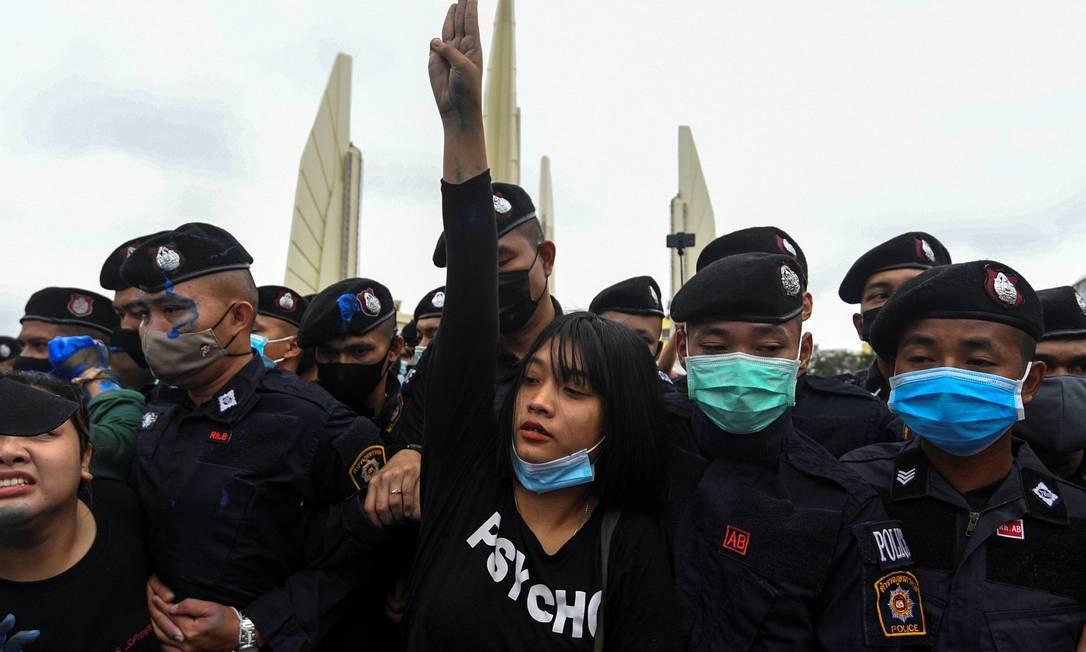 Uma ativista pró-democracia faz uma saudação com três dedos enquanto é detida por policiais Foto: CHALINEE THIRASUPA / REUTERS