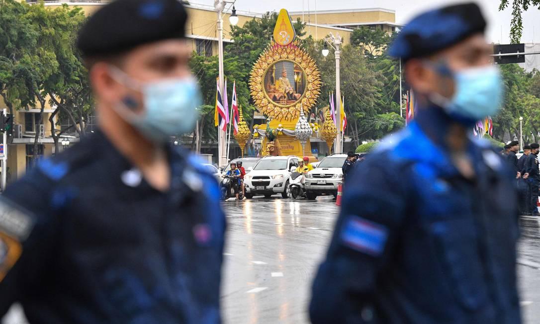Um retrato do rei Maha Vajiralongkorn da Tailândia é visto ao longo de uma estrada enquanto a polícia, salpicada de tinta azul lançada por manifestantes pró-democracia durante manifestação, monta guarda enquanto espera a passagem do comboio real Foto: MLADEN ANTONOV / AFP