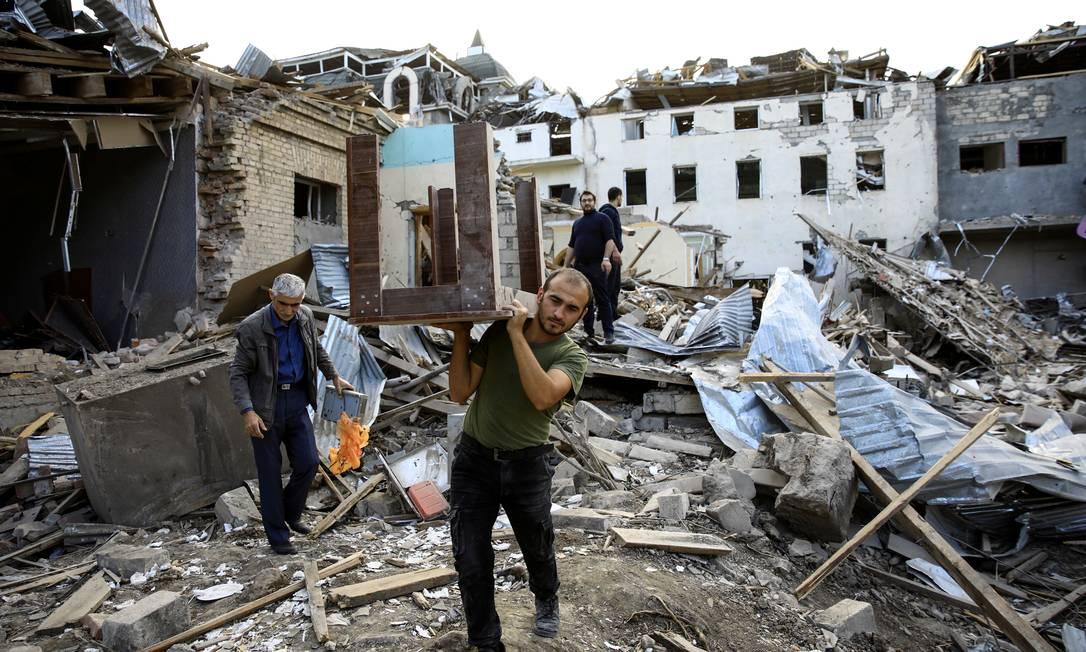 Homem carrega mesa entre as ruínas de um local após explosão de foguete na região separatista de Nagorno-Karabakh, na cidade de Ganja Foto: UMIT BEKTAS / REUTERS/11-10-2020