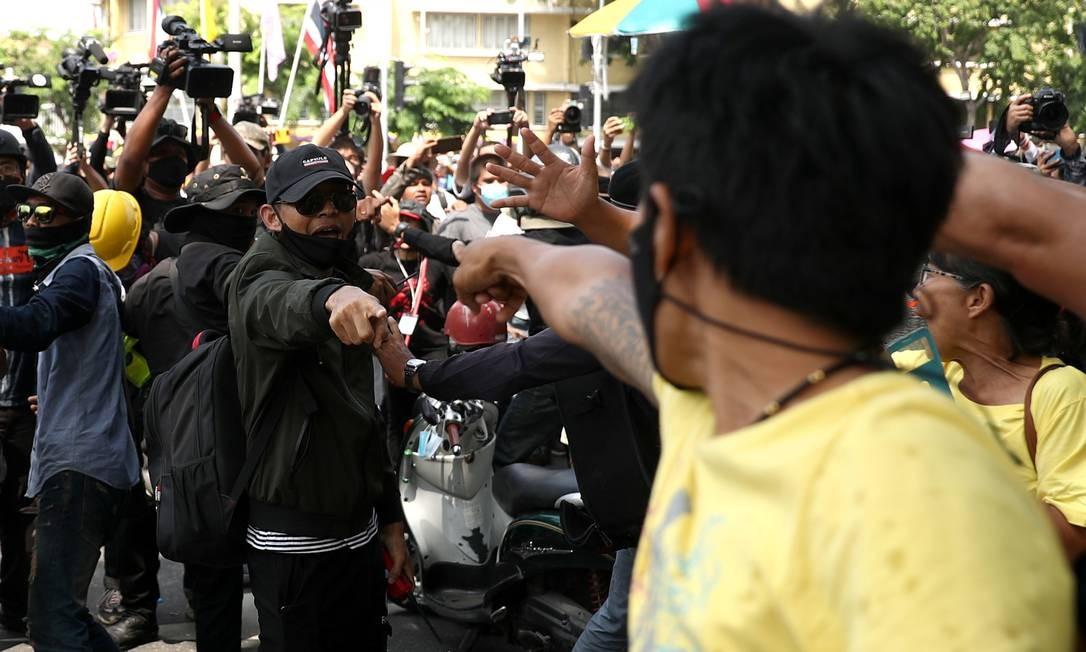 Monarquista e um manifestante antigovernamental se enfrentam durante manifestação pró-democracia, em Bangcoc Foto: ATHIT PERAWONGMETHA / REUTERS