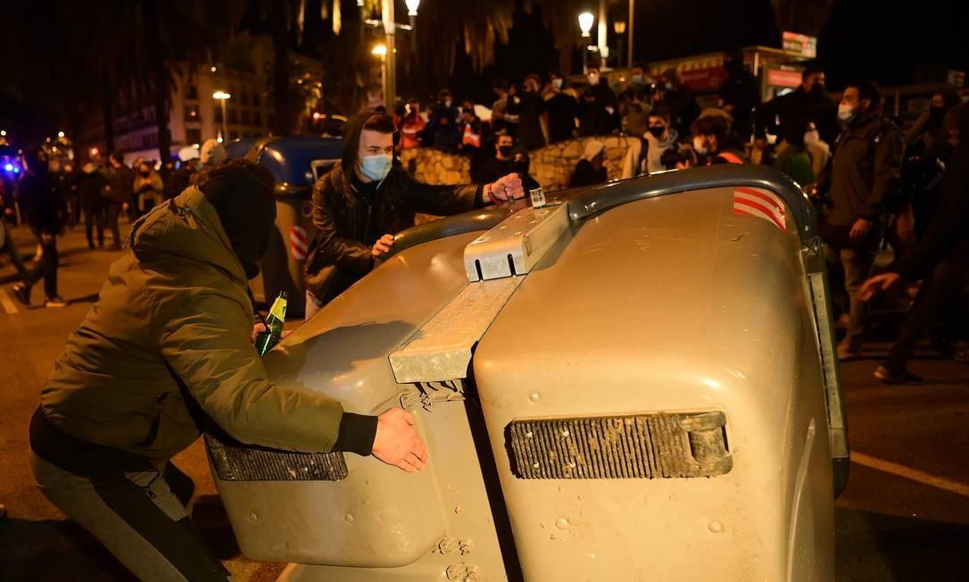 Manifestantes pró-independência empurram um contêiner de lixo durante protesto. Todos os réus foram absolvidos da acusação mais grave, a de rebelião, mas receberam penas de prisão que vão de 9 a 13 anos, gerando uma série de protestos nas ruas Foto: LLUIS GENE / AFP