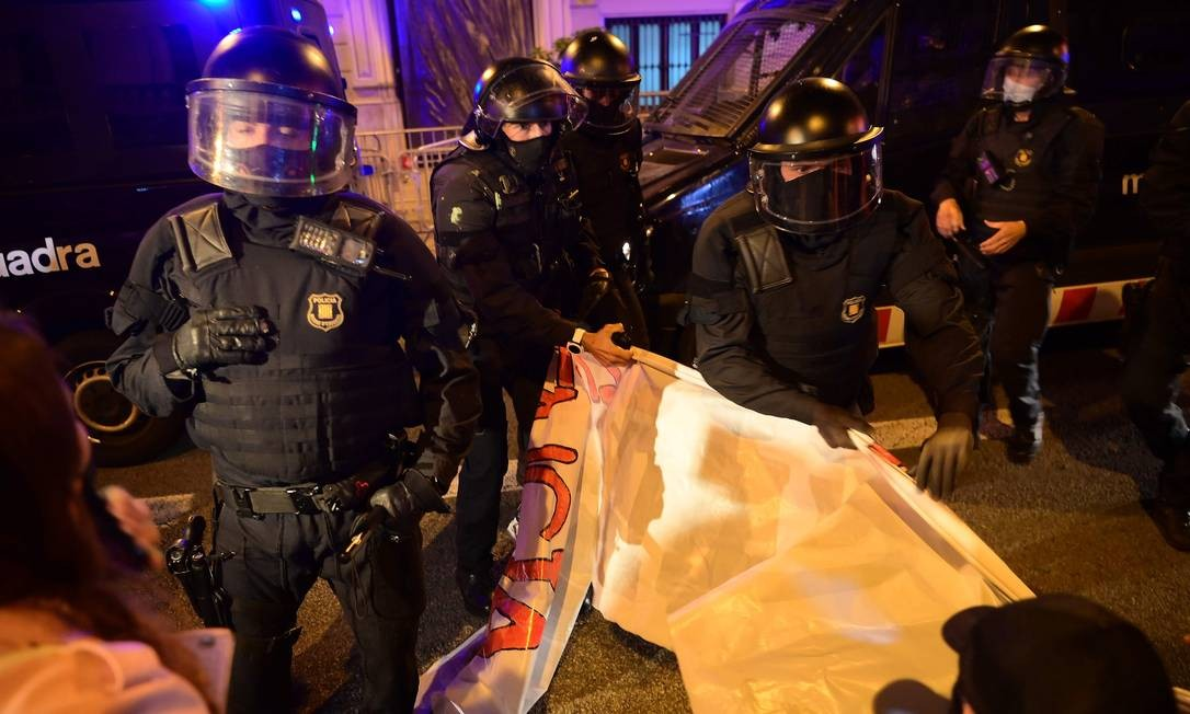 Membros da força policial regional da Catalunha retiram uma faixa de partidários dos Comitês de Defesa da República (CDR) da Catalunha Foto: LLUIS GENE / AFP