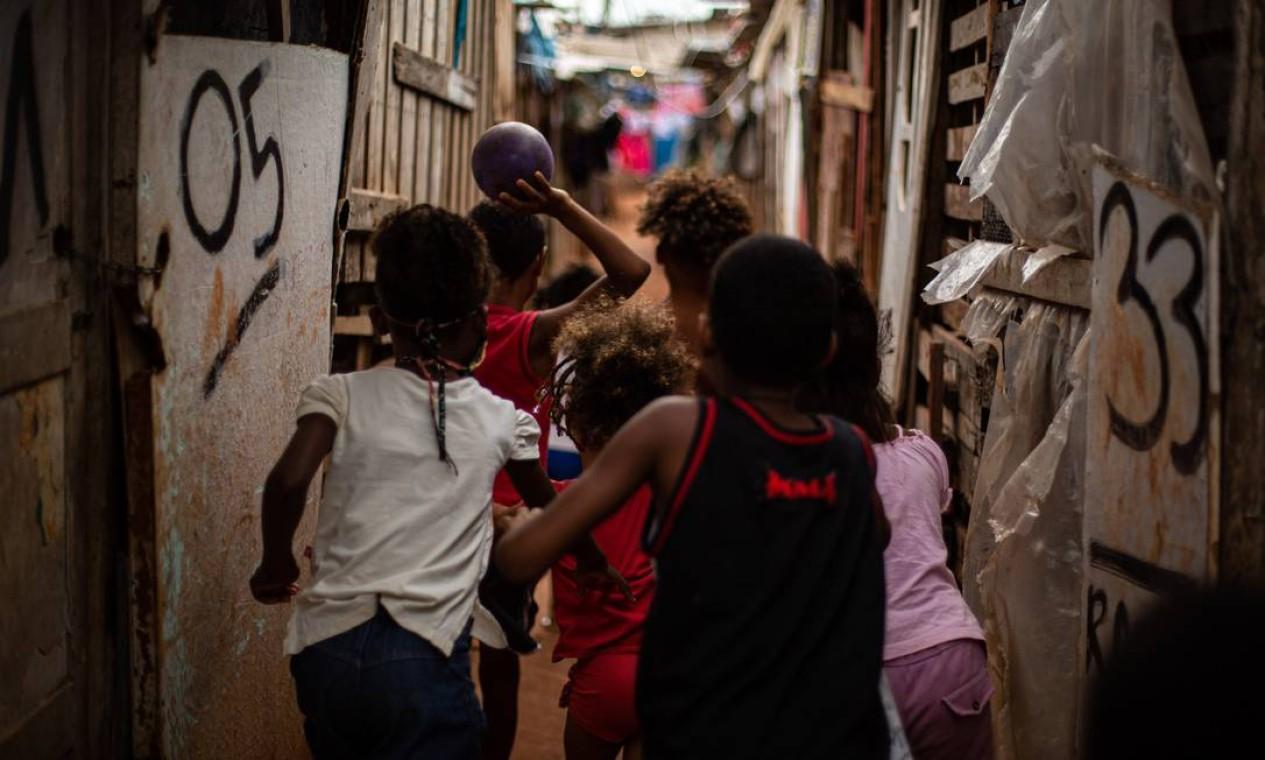 Crianças brincam entre barracos em comunidade localizada dentro de um dos conjuntos habitacionais da região do Jesuítas, em Santa Cruz, onde 200 famílias com renda abaixo da linha de pobreza vivem em barracos de madeira, papelão e compensado Foto: Hermes de Paula / Agência O Globo - 01/07/2020