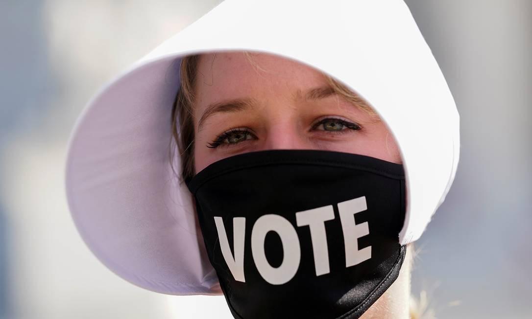 """Uma manifestante usa uma máscara e que se lê """"VOTE"""" enquanto participava de protesto fora da Suprema Corte dos EUA, em Washington Foto: KEVIN LAMARQUE / REUTERS"""