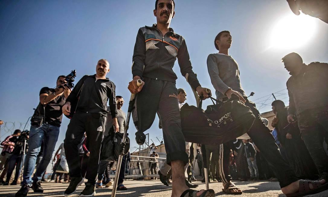 """Homens suspeitos de ter colaborado com o grupo do Estado Islâmico deixam a prisão de Alaya, administrada por curdos, na cidade de Qamishli, no nordeste da Síria. As Forças Democráticas da Síria (SDF) libertoumais de 600 prisioneiros acusados de """"atos de terrorismo"""" e supostas ligações com o grupo do Estado Islâmico Foto: DELIL SOULEIMAN / AFP"""
