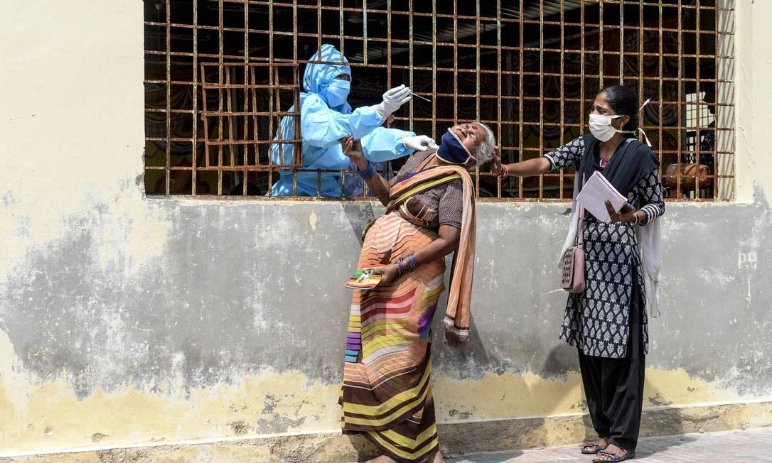 Mulher reage à coleta uma amostra de swab dela para testagem do coronavírus antes de ir a um campo médico para vítimas de enchentes em uma favela após fortes chuvas em Hyderabad, na Índia Foto: NOAH SEELAM / AFP