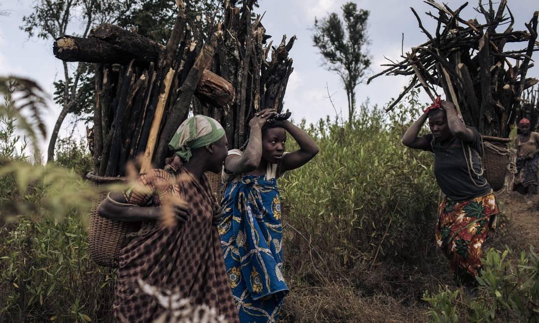 Mulheres carregam lenha para o campo de deslocados internos de Bijombo Foto: ALEXIS HUGUET / AFP