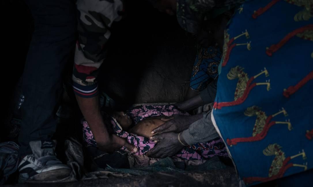 Parentes cuidam do corpo de Regina, uma menina deslocada de 5 anos que morreu por falta de assistência médica no campo de deslocados internos de Bijombo, província de Kivu do Sul, leste da República Democrática do Congo Foto: ALEXIS HUGUET / AFP