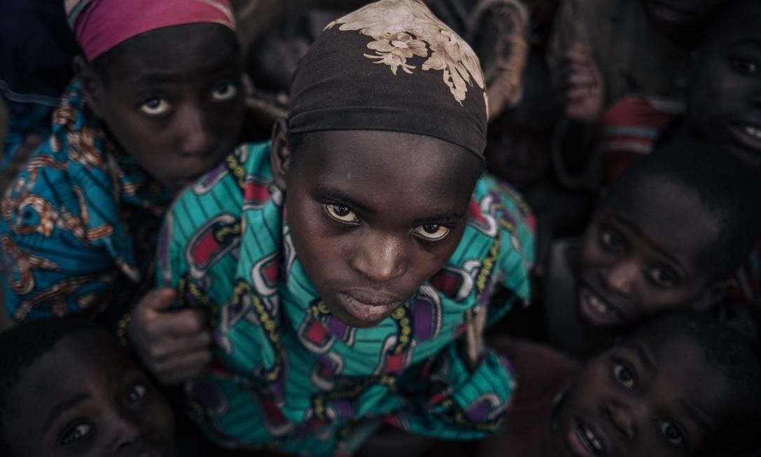 Meninas e meninos da comunidade de Bafuliru posam para uma fotografia no campo de deslocados internos de Bijombo Foto: ALEXIS HUGUET / AFP