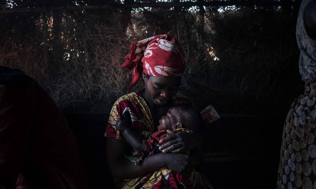 Mulher refugiados cuida de seu filho que sofre de diarreia aguda no centro de saúde improvisado do campo de deslocados internos de Bijombo, Província de Kivu do Sul, leste da República Democrática do Congo Foto: ALEXIS HUGUET / AFP