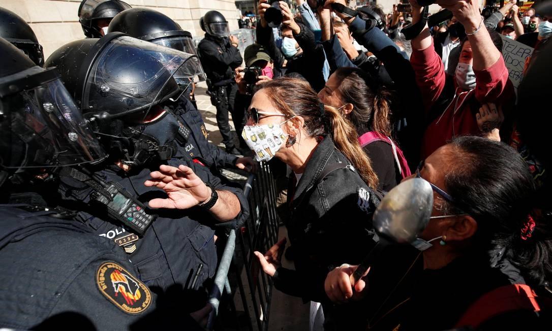 Trabalhadores enfrentam policiais durante um protesto contra autoridades ordenando o fechamento de bares e restaurantes Foto: ALBERT GEA / REUTERS