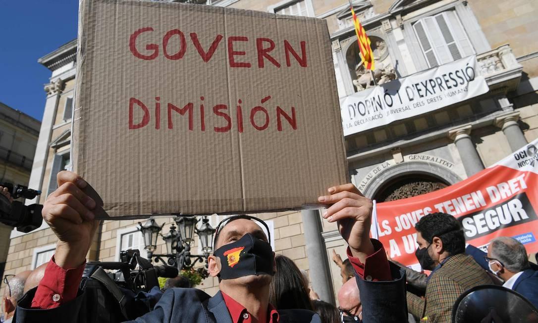 Um manifestante segura um cartaz exigindo a renúncia do governo regional Foto: LLUIS GENE / AFP