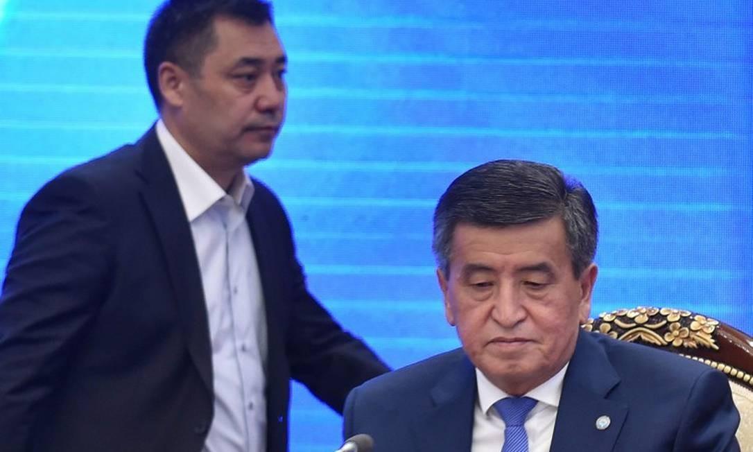 Em pé, Sadyr Japarov, primeiro-ministro e presidente interino, ao lado do ex-preisdente Sooronbai Jeenbekov, durante sessão no Parlamento Foto: VYACHESLAV OSELEDKO / AFP