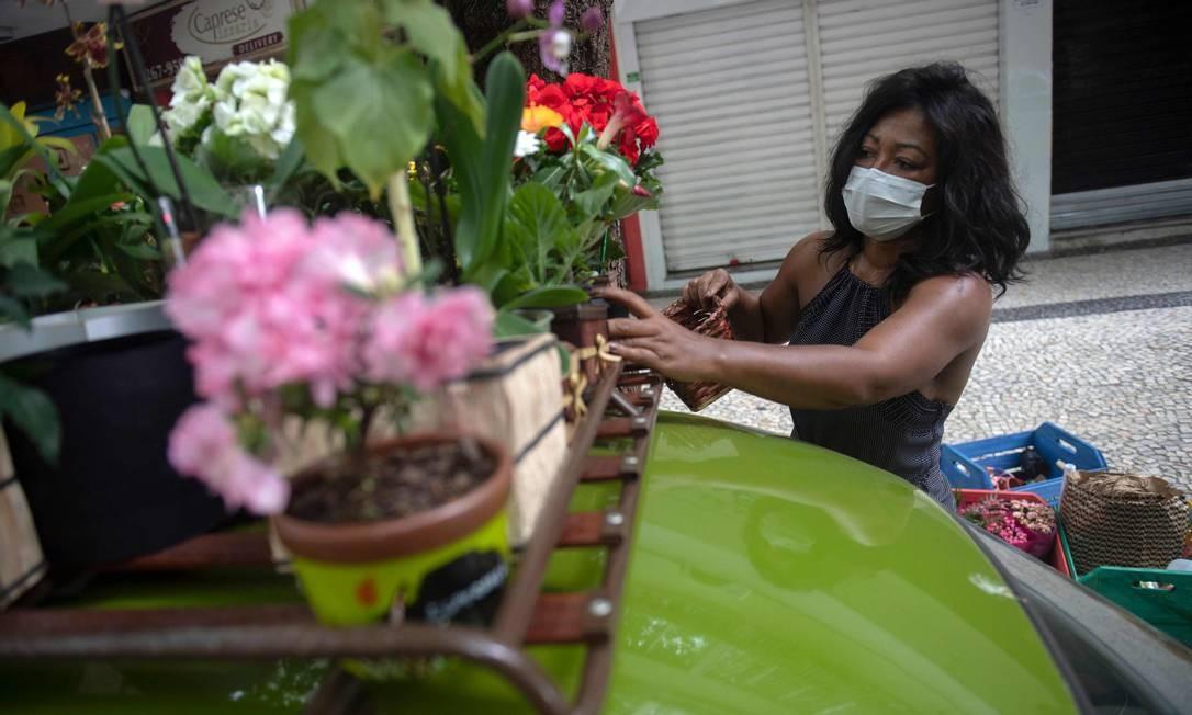 Roberta arruma seus arranjos de flores sobre bagageiro instalado sobre o carro Foto: MAURO PIMENTEL / AFP