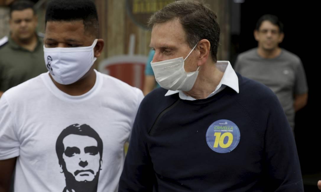 Crivella ao lado de apoiador com camisa estampada pelo rosto de Jair Bolsonaro, durante visita a obras na Avenida Brasil Foto: Gabriel de Paiva / Agência O Globo