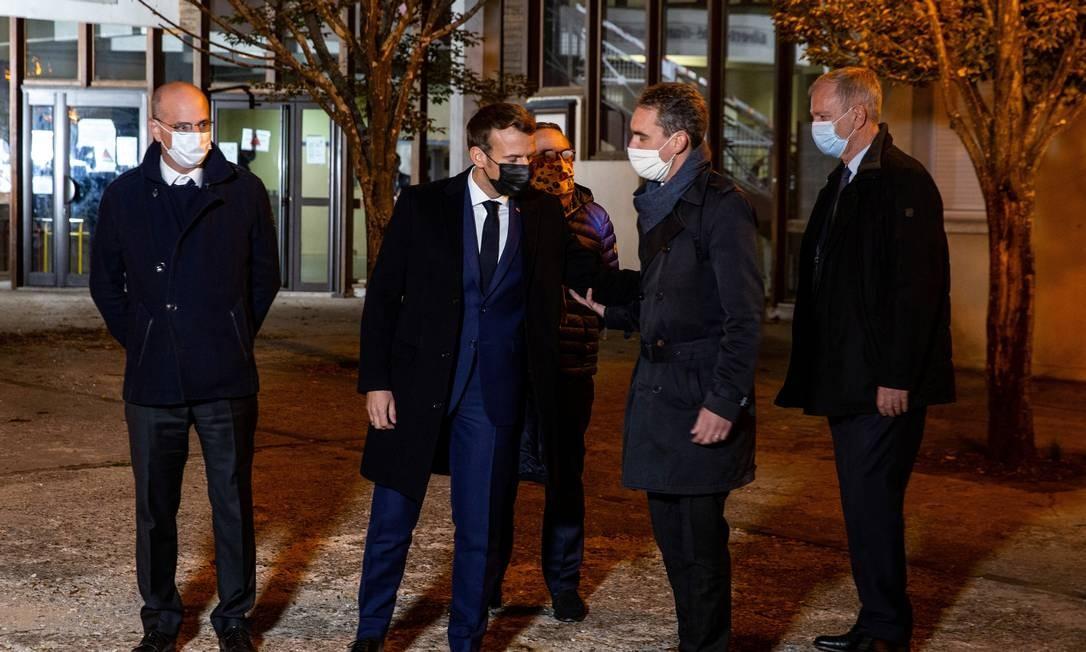 Macron (ao centro) visita o local em que o professor foi atacado com faca Foto: POOL / REUTERS