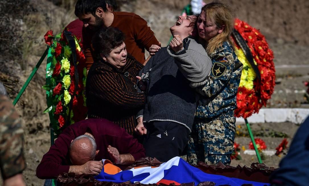 Uma mãe chora sobre o caixão de seu companheiro em Stepanakert durante os combates entre Armênia e Azerbaijão. O presidente do Azerbaijão, Ilham Aliyev, jurou se vingar da Armênia depois um ataque de míssil matou 12 pessoas adormecidas na cidade de Ganja, uma escalada dramática no conflito sobre a disputada região de Nagorno-Karabakh Foto: ARIS MESSINIS / AFP