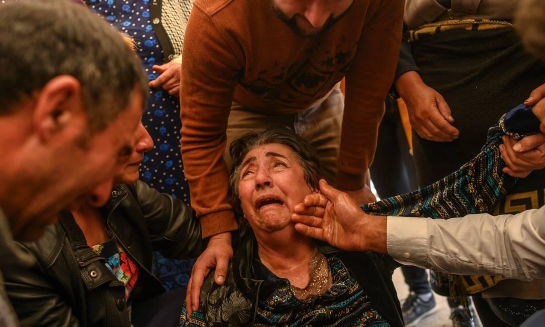 Familiares choram em velório de vítima de um foguete que atingiu sua casa, na cidade de Ganja, Azerbaijão, durante os combates na região separatista de Nagorno-Karabakh Foto: BULENT KILIC / AFP