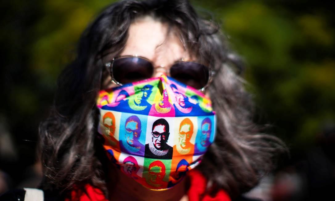 Mulher usa uma máscara de rpoteção com imagens da falecida juíza Ruth Bader Ginsburg enquanto as pessoas participam da Marcha das Mulheres no parque Washington Square em Manhattan, Nova Iorque Foto: EDUARDO MUNOZ / REUTERS