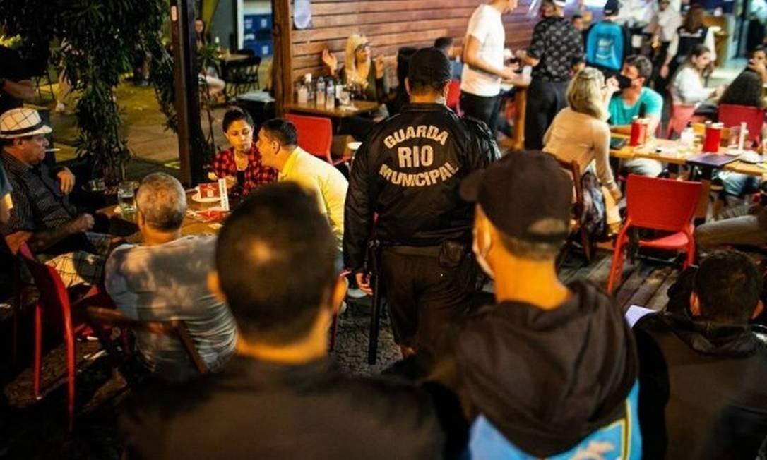 Guarda municipal circula entre mesas de bar onde as pessoas estão sem máscara Foto: Hermes de Paula/17-7-2020