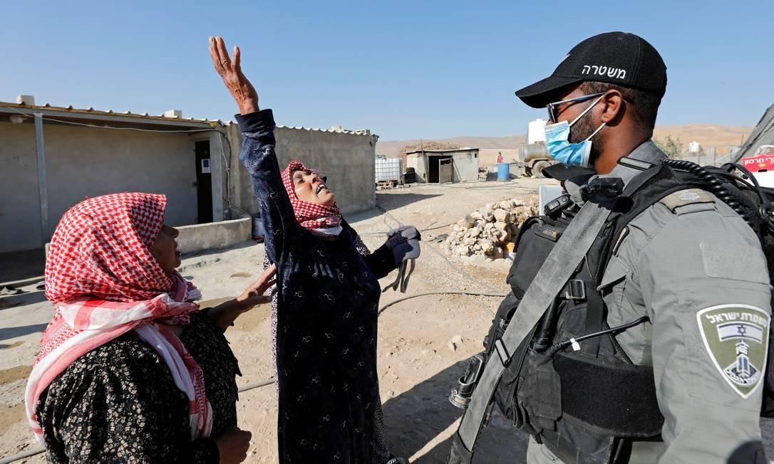 Mulher palestina reage a policial de fronteira israelense enquanto as forças israelenses demolem sua casa e galpão, perto de Hebron, na Cisjordânia ocupada por Israel Foto: MUSSA ISSA QAWASMA / REUTERS