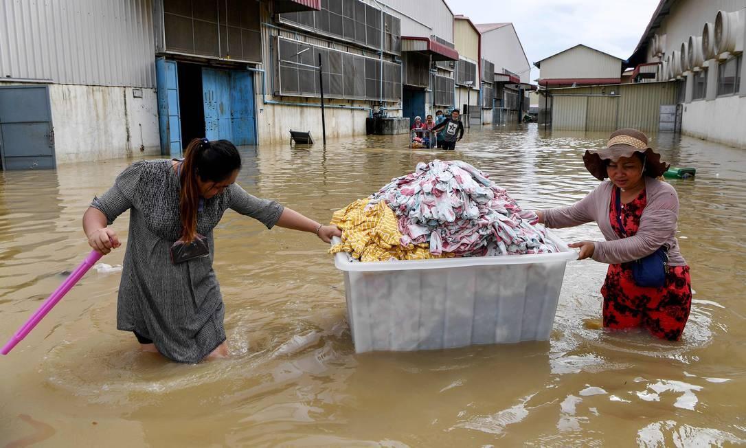 Trabalhadores resgatam roupas de uma fábrica em meio a enchentes nos arredores de Phnom Penh, capital do Camboja Foto: TANG CHHIN SOTHY / AFP