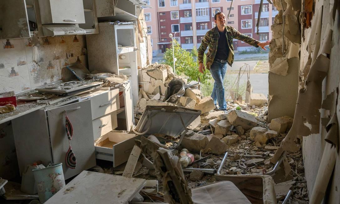 Homem verifica apartamento de seu vizinho danificado durante conflito na região separatista de Nagorno-Karabakh, na cidade de Terter Foto: BULENT KILIC / AFP/18-10-2020