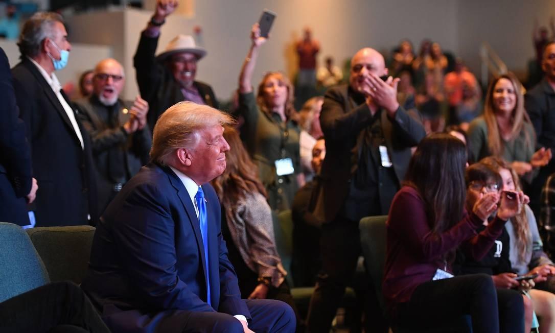 Em luta para recuperar terreno perdido, Trump sorri enquanto participa de um culto religioso. Presidente raramente vai à igreja, mas continua popular entre os cristãos evangélicos por sua oposição ao aborto e por nomear juízes conservadores Foto: MANDEL NGAN / AFP
