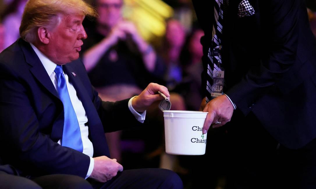 O presidente dos EUA deposita dinheiro em um recipiente enquanto participa de culto religioso na Igreja Internacional de Las Vegas Foto: CARLOS BARRIA / REUTERS
