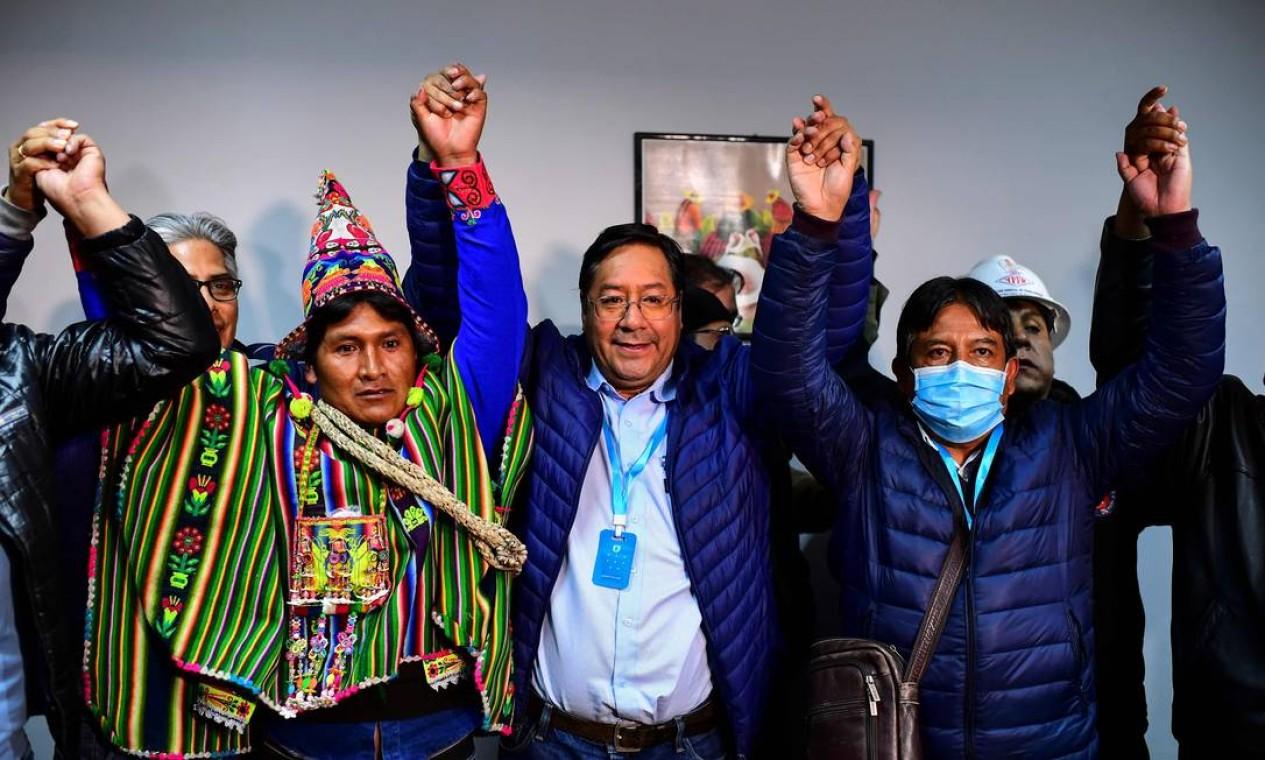 Apontado pelas pesquisas de boca de urna como presidente eleito da Bolívia, Luis Arce (ao centro), de 57 anos, comemora, em La Paz, a vitória no primeiro turno das eleições presidenciais de domingo Foto: RONALDO SCHEMIDT / AFP